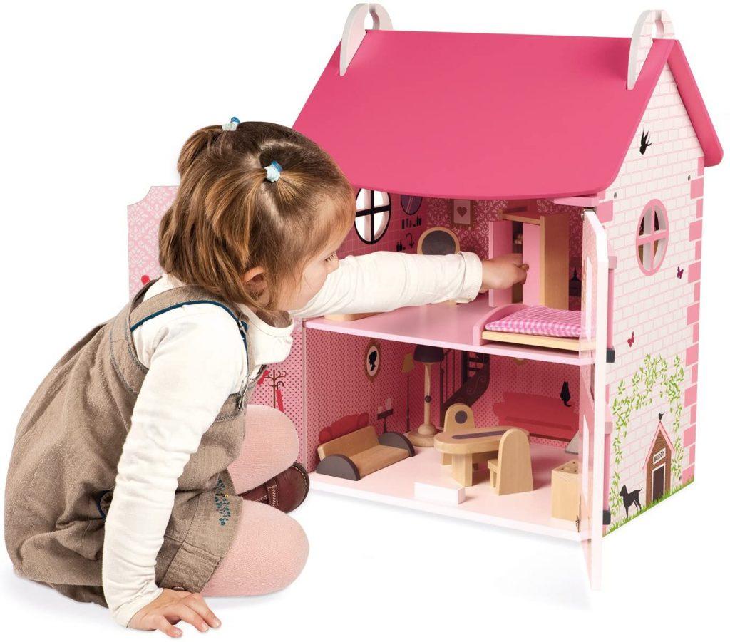 Petite fille en train de jouer avec la maison de poupée valise Mademoiselle, de la marque Janod.